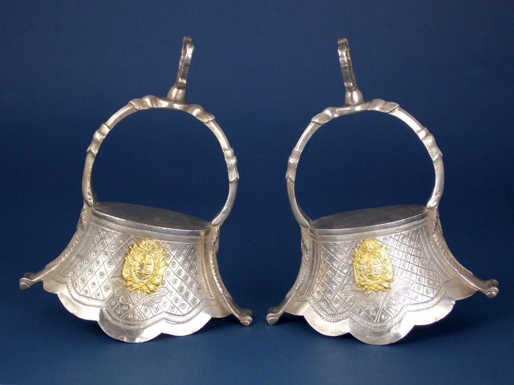 Gran par de estribos tipo campana en plata cincelada Flores con Escudo Nacional antiguo de bronce dorado en ambos lados